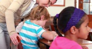 Όμορφος δάσκαλος που βοηθά το μαθητή στο γραφείο του απόθεμα βίντεο