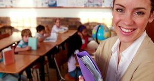 Όμορφος δάσκαλος που χαμογελά στη κάμερα στην κορυφή της τάξης απόθεμα βίντεο