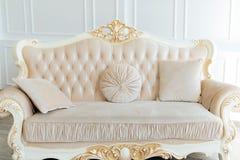 Όμορφος άσπρος ακριβός καναπές μέσα στο ελαφρύ εσωτερικό στοκ φωτογραφίες