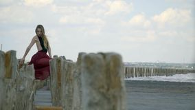 Όμορφος ένας ξανθός σε ένα φόρεμα κρατά επάνω στις ξύλινες θέσεις και κρεμά στον αέρα στη μέση της εκβολής ανάμεσα φιλμ μικρού μήκους