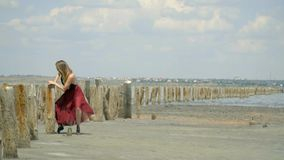 Όμορφος ένας ξανθός σε ένα φόρεμα κρύβει πίσω από τις ξύλινες θέσεις στη μέση της εκβολής ανάμεσα στις εγκαταλειμμένες αλατισμένε φιλμ μικρού μήκους