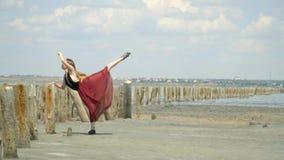 Όμορφος ένας ξανθός σε ένα φόρεμα που χορεύει και στέκεται σε μια σειρά κοντά στις ξύλινες θέσεις στη μέση της εκβολής ανάμεσα φιλμ μικρού μήκους