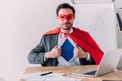 όμορφος έξοχος επιχειρηματίας στη μάσκα και ακρωτήριο που παρουσιάζει μπλε πουκάμισο Στοκ φωτογραφίες με δικαίωμα ελεύθερης χρήσης