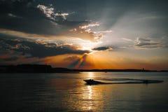 Όμορφος ήλιος πίσω από τα σύννεφα, τη θάλασσα και τη βάρκα Στοκ Εικόνες