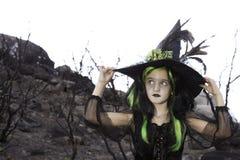 Όμορφος λίγη μάγισσα που κρατά το καπέλο μαγισσών της και που κοιτάζει μακριά Στοκ Εικόνα