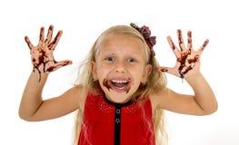 Όμορφος λίγο κορίτσι με τα μακριά ξανθά μαλλιά και μπλε μάτια που φορούν το κόκκινο φόρεμα που παρουσιάζει βρώμικα χέρια Στοκ Φωτογραφίες