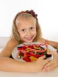 Όμορφος λίγο κορίτσι που τρώει το σύνολο πιάτων της καραμέλας καραμελών και των γλυκών τροφίμων Στοκ Εικόνες