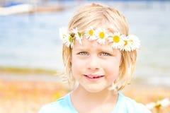 Όμορφος λίγο ξανθό κορίτσι με μια κορώνα των μαργαριτών Στοκ Φωτογραφία