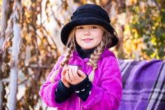 Όμορφος λίγο ξανθό κορίτσι σε έναν καφέ κατανάλωσης καπέλων ή τσάι στο πάρκο φθινοπώρου το παιδί πίνει το τσάι στο πάρκο Στοκ φωτογραφία με δικαίωμα ελεύθερης χρήσης