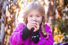 Όμορφος λίγο ξανθό κορίτσι σε έναν καφέ κατανάλωσης καπέλων ή τσάι στο πάρκο φθινοπώρου το παιδί πίνει το τσάι στο πάρκο Στοκ Εικόνα