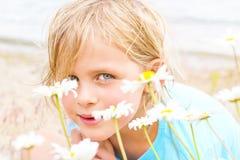 Όμορφος λίγο ξανθό κορίτσι σε ένα μπάλωμα των μαργαριτών Στοκ Εικόνες