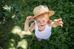 Όμορφος λίγο παιδί με το καπέλο αχύρου που φαίνεται επάνω και κυματισμός χεριών Στοκ φωτογραφίες με δικαίωμα ελεύθερης χρήσης