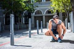 Όμορφος αθλητής που δένει τις δαντέλλες παπουτσιών του Στοκ Εικόνες