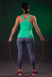Όμορφος αθλητικός, στάση γυναικών ικανότητας, που θέτει με ένα σχοινί άλματος σε ένα γκρίζο υπόβαθρο με ένα πράσινο backlight Στοκ εικόνες με δικαίωμα ελεύθερης χρήσης