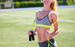Όμορφος αθλητισμός ξανθός η γυναίκα με ένα σχοινί άλματος στο στάδιο S Στοκ Εικόνες