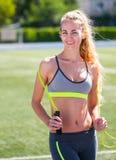 Όμορφος αθλητισμός ξανθός η γυναίκα με ένα σχοινί άλματος στο στάδιο S Στοκ Εικόνα