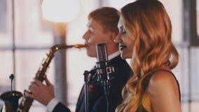 Όμορφος αοιδός τζαζ που αποδίδει στη σκηνή με το χορό saxophonist Επίκεντρα απόθεμα βίντεο