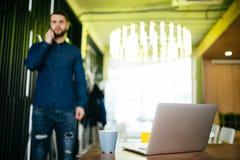 Όμορφος αρσενικός επιχειρηματίας που στέκεται στο γραφείο και το ομιλούν τηλέφωνό του στην αρχή Στοκ Φωτογραφίες