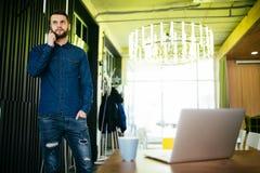 Όμορφος αρσενικός επιχειρηματίας που στέκεται στο γραφείο και το ομιλούν τηλέφωνό του στην αρχή Στοκ Εικόνες