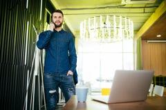 Όμορφος αρσενικός επιχειρηματίας που στέκεται στο γραφείο και το ομιλούν τηλέφωνό του στην αρχή Στοκ εικόνα με δικαίωμα ελεύθερης χρήσης