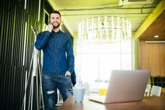 Όμορφος αρσενικός επιχειρηματίας που στέκεται στο γραφείο και το ομιλούν τηλέφωνό του στην αρχή Στοκ Φωτογραφία