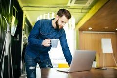 Όμορφος αρσενικός επιχειρηματίας που στέκεται στο γραφείο του και σε κάτι στην οθόνη του υπολογιστή του Στοκ εικόνα με δικαίωμα ελεύθερης χρήσης