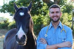 Όμορφος αρσενικός κτηνίατρος που χαμογελά κοντά σε ένα άλογο Στοκ εικόνες με δικαίωμα ελεύθερης χρήσης