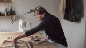 Όμορφος αρσενικός ράφτης με την εργασία κυβερνητών στο ράψιμο του εργαστηρίου απόθεμα βίντεο