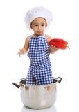 Όμορφος αρχιμάγειρας παιδιών στο λαχανικό εκμετάλλευσης δοχείων Στοκ Εικόνες