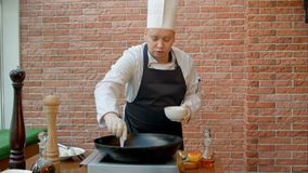 Όμορφος αρχιμάγειρας που προετοιμάζει το τηγάνι με το κτύπημα και που μιλά στη κάμερα Στοκ Φωτογραφίες