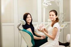 Όμορφος ασθενής γυναικών που έχει την οδοντική θεραπεία στο γραφείο του οδοντιάτρου Ο γιατρός κρατά το ιατρικό σαγόνι στοκ φωτογραφίες