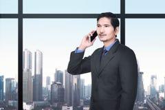 Όμορφος ασιατικός επιχειρηματίας που μιλά στο κινητό τηλέφωνο Στοκ Φωτογραφία