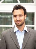 Όμορφος λατινικός επιχειρηματίας που χαμογελά μπροστά από το γραφείο του στοκ φωτογραφία με δικαίωμα ελεύθερης χρήσης