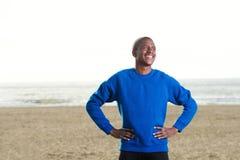Όμορφος αφρικανικός τύπος που στέκεται στην παραλία στην μπλε μπλούζα Στοκ Εικόνες