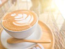Όμορφος αφρός στο φλυτζάνι καφέ στον πίνακα με το φως ήλιων Στοκ Φωτογραφίες