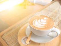 Όμορφος αφρός στο φλυτζάνι καφέ στον πίνακα με το φως ήλιων Στοκ Εικόνες