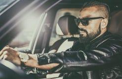 Όμορφος βάναυσος νεαρός άνδρας πίσω από τη ρόδα ενός αυτοκινήτου πολυτέλειας Στοκ Εικόνα