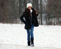 Όμορφος βέβαιος πράσινος έφηβος ματιών που περπατά κάτω από το χιόνι χιονίζοντας στοκ φωτογραφίες