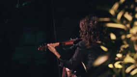 Όμορφος βιολιστής κοριτσιών στα μαύρα ενδύματα και τη μακριά σγουρή τρίχα που παίζει το βιολί στη σκηνή Δροσερός μουσικός κοριτσι απόθεμα βίντεο