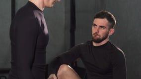 Όμορφος γενειοφόρος αρσενικός προσωπικός εκπαιδευτής που βοηθά το νεαρό άνδρα στη γυμναστική απόθεμα βίντεο