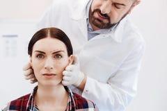 Όμορφος γενειοφόρος γιατρός που στέκεται πίσω από τον ασθενή του Στοκ φωτογραφία με δικαίωμα ελεύθερης χρήσης