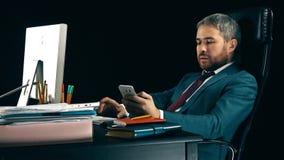 Όμορφος γενειοφόρος επιχειρηματίας που εργάζεται στον υπολογιστή και που χρησιμοποιεί το smartphone του Μαύρη ανασκόπηση Στοκ φωτογραφίες με δικαίωμα ελεύθερης χρήσης