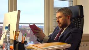 Όμορφος γενειοφόρος επιχειρηματίας που εργάζεται στον υπολογιστή του και που γράφει στο κόκκινο σημειωματάριό του στο γραφείο Στοκ Φωτογραφίες