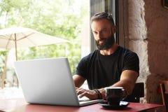 Όμορφος γενειοφόρος επιχειρηματίας που φορά το μαύρο ξύλινο επιτραπέζιο αστικό καφέ lap-top μπλουζών λειτουργώντας Νέο σημειωματά Στοκ φωτογραφίες με δικαίωμα ελεύθερης χρήσης