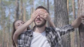 Όμορφος γενειοφόρος νεαρός άνδρας πορτρέτου στο δάσος πεύκων, το κορίτσι που καλύπτει τα μάτια του με τα χέρια από την πίσω κινημ απόθεμα βίντεο