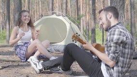 Όμορφος γενειοφόρος νεαρός άνδρας που παίζει ukulele στη σκηνή ενώ αρκετά νέα ευτυχής συνεδρίαση γυναικών μπροστά από τον Αγάπη φιλμ μικρού μήκους