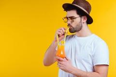 όμορφος γενειοφόρος νεαρός άνδρας στο καπέλο και γυαλιά ηλίου που πίνουν το θερινό κοκτέιλ Στοκ Εικόνες