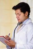 Όμορφος γιατρός με ένα στηθοσκόπιο γύρω από το λαιμό του, που γράφει στις σημειώσεις σημειωματάριών του στο υπόβαθρο γραφείων Στοκ Εικόνες