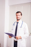 Όμορφος γιατρός με το στηθοσκόπιο arround ο λαιμός του στο νοσοκομείο σχετικά με Στοκ Εικόνα