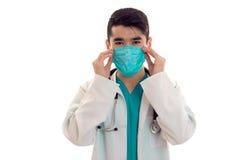 Όμορφος γιατρός νεαρών άνδρων σε ομοιόμορφο και μάσκα με το stethoscop στο λαιμό του που κοιτάζει και που θέτει στη κάμερα που απ Στοκ Εικόνες